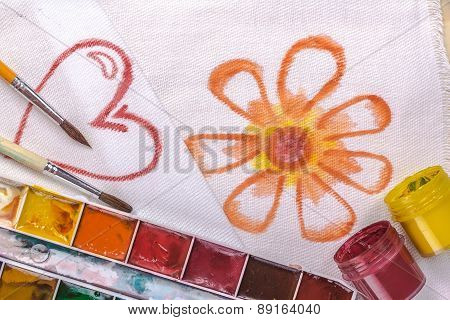 artist's brush on a background painted flower and heart