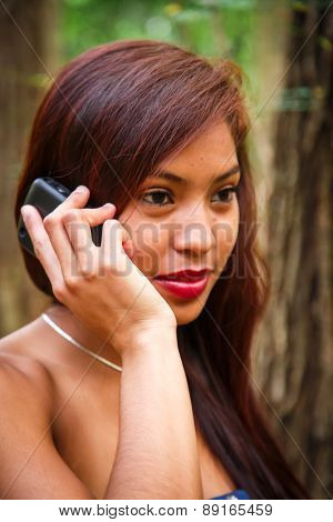 Atractive Latin Woman Using Phone At Forest With Blue Dress