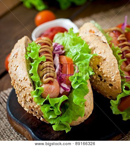 Hotdog with ketchup mustard and lettuce on wooden background