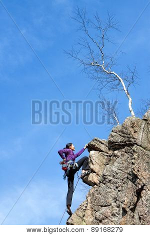 Female Rock Climber On A Cliff.
