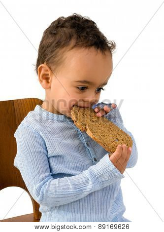 Cute little African boy eating a slice of wholemeal bread