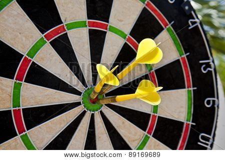 dart board with three darts in bullseye