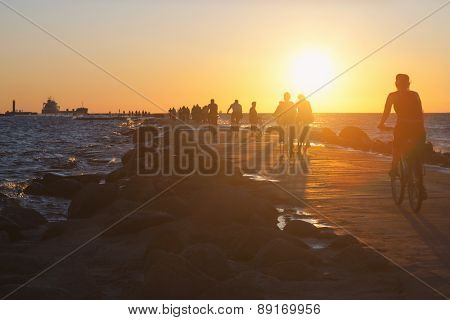 People On Bikes Ride Along The Dike In The Sea At Sunset
