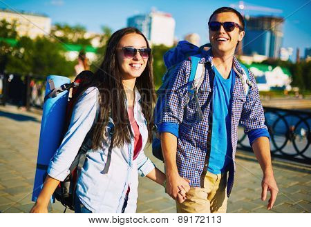 Affectionate couple with rucksacks enjoying weekend walk around the city