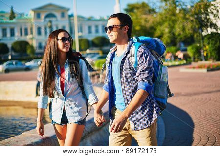 Affectionate travelers with rucksacks enjoying walk in the city