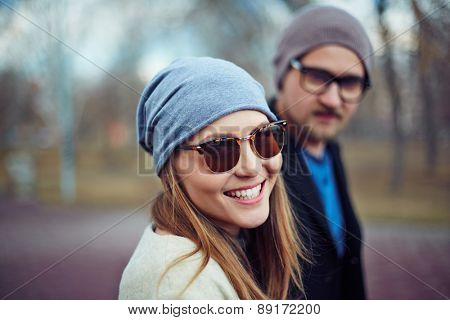 Happy girl in cap and sunglasses looking at camera with her boyfriend on background