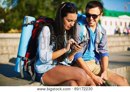 Young couple with rucksacks consulting mobile navigator