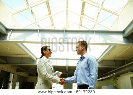 Happy business people shaking hands after striking deal