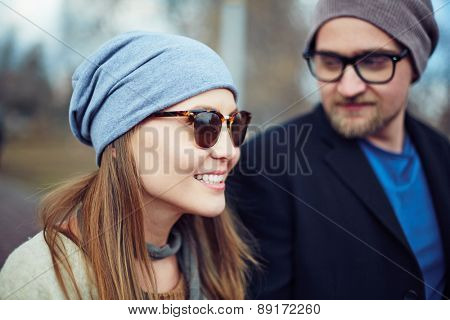 Happy young woman in cap and sunglasses on background of her boyfriend