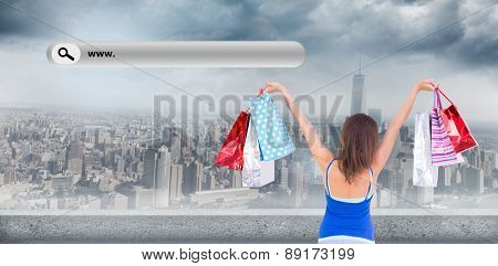 Rear view of a brunette woman raising shopping bags against large city