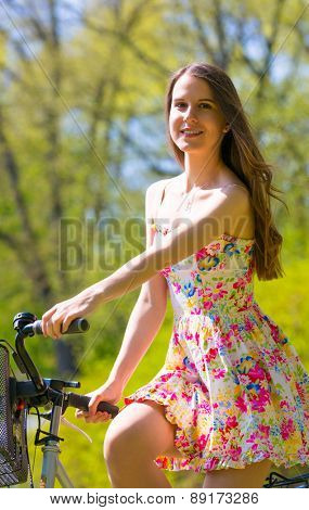 Young woman in short colorful dress with long hair rides a bicycle with  tour summer city park, look and smile to camera