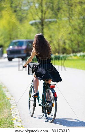 Young woman in short black dress with long hair rides a bicycle in summer city park, Back to camera