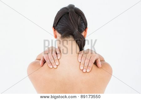 Brunette touching her painful shoulders on white background