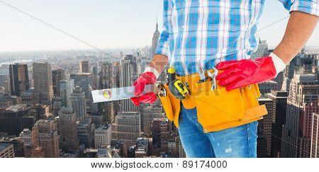 Midsection of handyman holding spirit level against new york