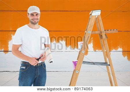 Man holding paint roller while standing by ladder against painted blue wooden planks