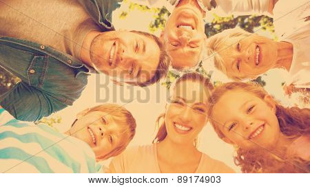 Low angle portrait of an extended family forming huddle in the park