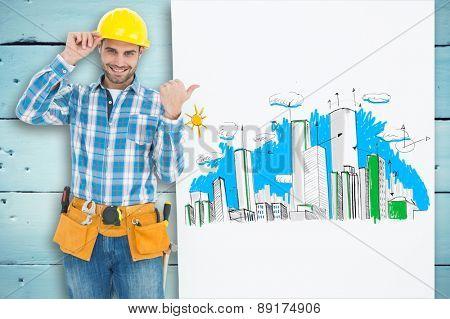 Happy repairman pointing towards blank billboard against painted blue wooden planks