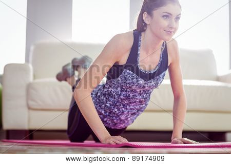 Fit woman doing press up on exercise mat at home in the living room