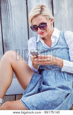 Pretty blonde woman wearing sun glasses and texting with her mobile phone on wooden background