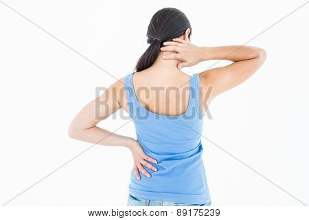 Pretty brunette suffering from neck pain on white background