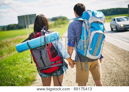 Young travelers with backpacks standing by road