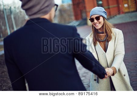 Young female in stylish clothes and sunglasses looking at her boyfriend outdoors