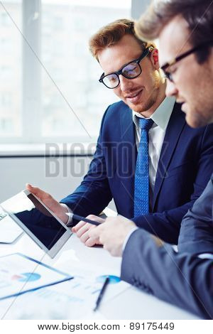 Young businessman listening to colleague explanations at meeting