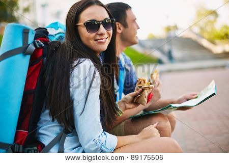 Young woman with rucksack and snack looking at camera