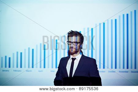Young businessman standing by wall with chart on it