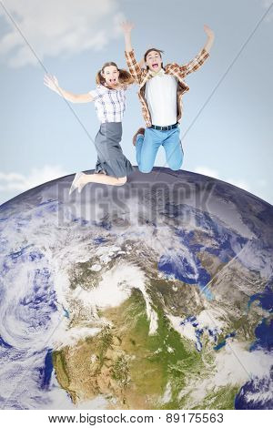Geeky hipsters jumping and smiling against blue sky