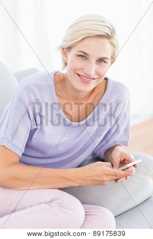Pretty blonde woman texting with her mobile phone in the living room