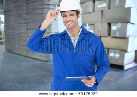 Happy supervisor wearing hard hat while holding clip board against cardboard boxes in warehouse