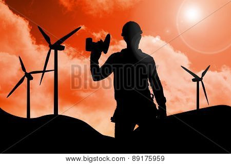 Handyman wearing tool belt while holding power drill against sky and mountains