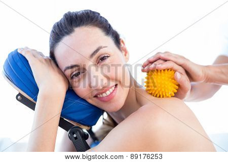 Woman having back massage with massage ball in medical office