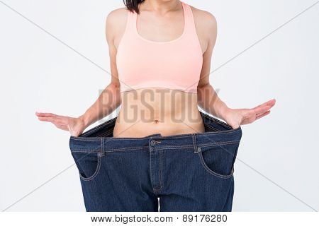 Woman showing her waist after losing weight on white background