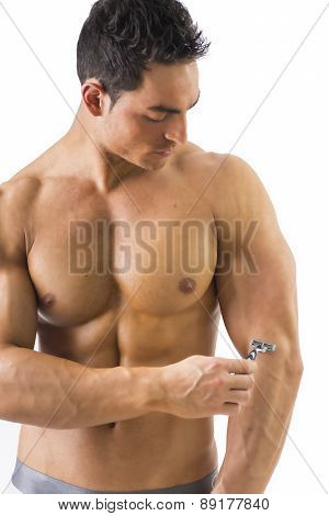 Shirtless muscular man shaving arm with manual razor