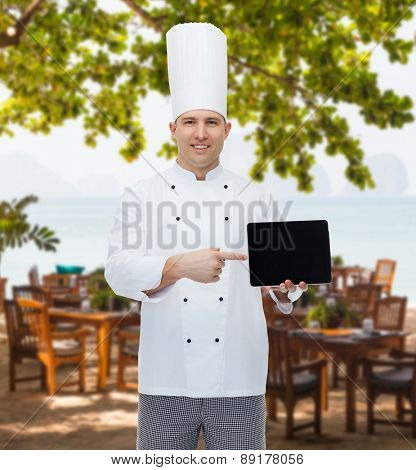 cooking, profession and people concept - happy male chef cook showing tablet pc computer black blank screen over restaurant lounge on beach