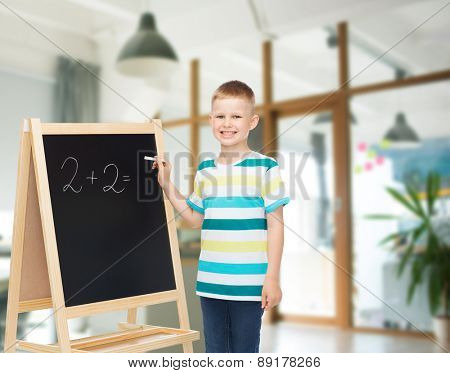 people, childhood, mathematics and education concept - happy little boy with blackboard and chalk writing math exercise over school class room background