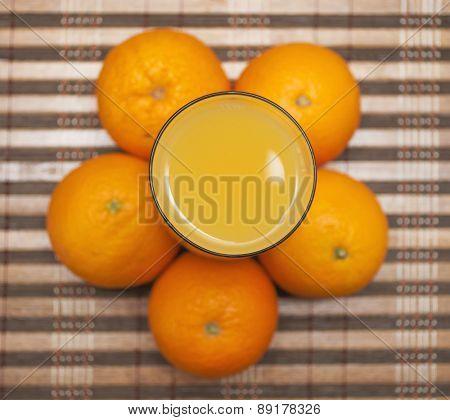 Orange juice and fresh oranges around glass
