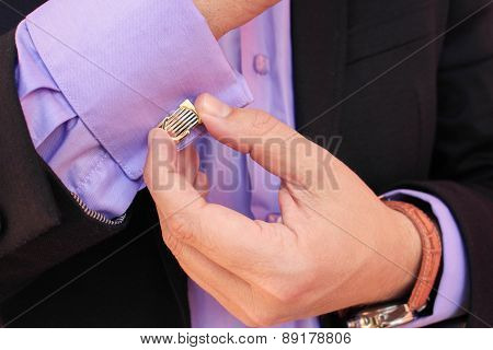 Male hand buttons cufflinks in purple shirt