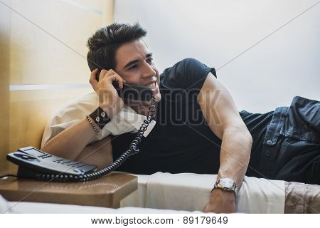 Smiling Young Man Lying in Bed and Talking on Telephone
