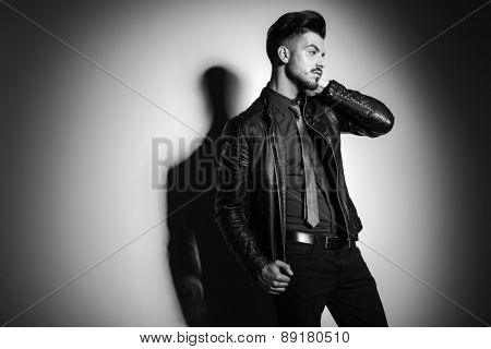 Side view picture of a handsome business man looking away from the camera while holding his hand to his neck.