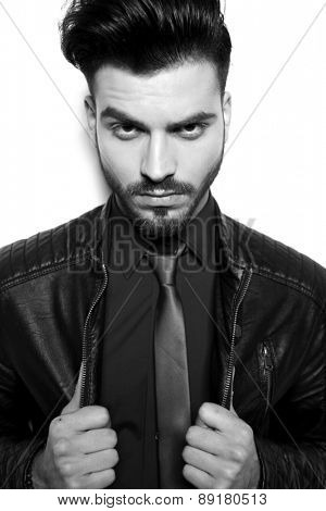 Close up picture of a young handsome business man pulling his leather jacket.