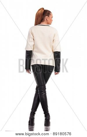 Rear view of a sexy young fashion woman standing with her legs crossed on isolated background.