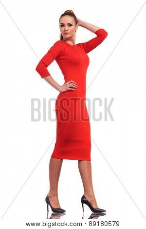 Attractive fashion woman wearing a slim red dress walking on studio background.