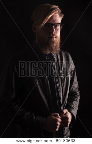 Portrait of a blond casual man fixing his jacket while looking at the camera.