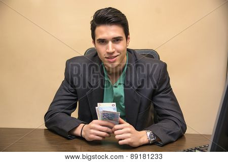 Young Businessman, Sitting at his Worktable, Counting Cash on Hand