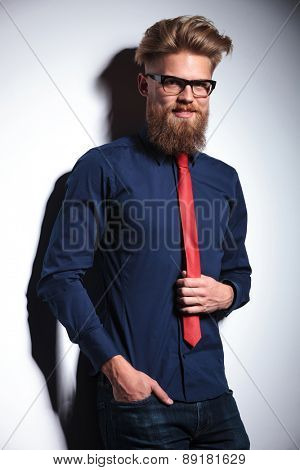 Handsome business man leaning on a wall while pulling his red tie.