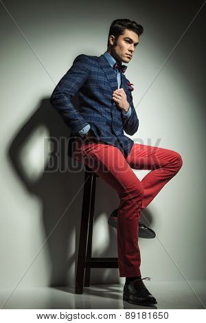 Full body picture of a fashion man sitting on a stool while fixing his collar.