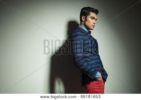 Side view picture of a handsome fashion man standing with his hand in pockets.